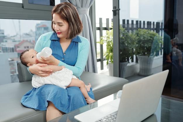 Jovem mãe alimentando seu filho com fórmula em garrafa de plástico durante o intervalo após trabalhar no laptop