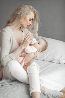 Jovem mãe alimentando sua filha bebê fofo com garrafa de fórmula infantil. mulher com seu bebê recém-nascido em casa. mãe cuidando de uma criança. alternativa à amamentação.