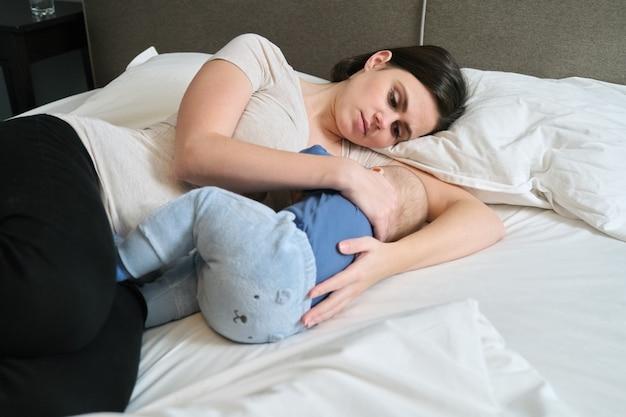 Jovem mãe amamentando seu filho, mãe amamentando e abraçando o bebê, mãe e criança deitam-se juntas em casa na cama, bebê comendo e adormecendo