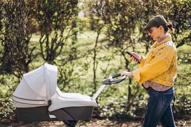 Jovem mãe andando com carrinho de bebê no parque e usando o telefone