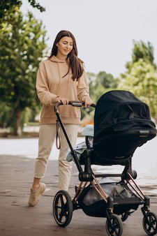 Jovem mãe andando com carrinho de bebê no parque