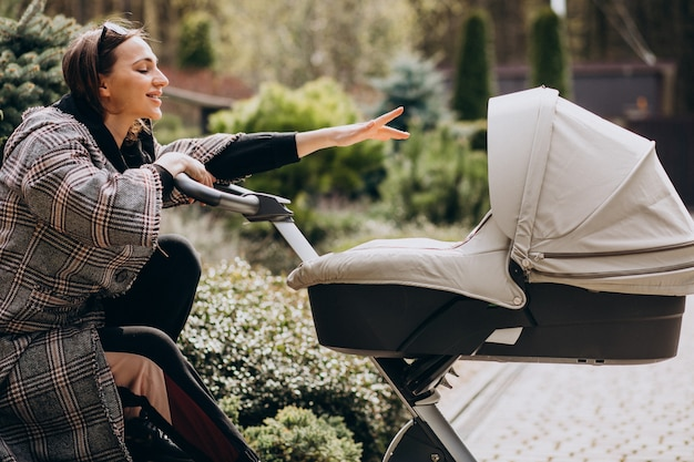 Jovem mãe andando com carrinho de bebê no quintal