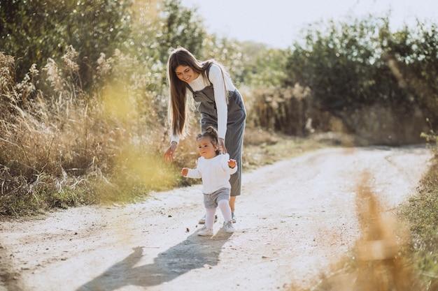 Jovem mãe andando com seu bebê no campo