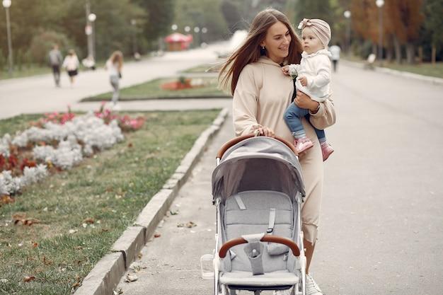 Jovem mãe andando em um parque de outono com transporte