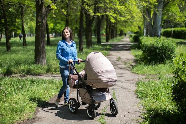 Jovem mãe andando um carrinho no parque