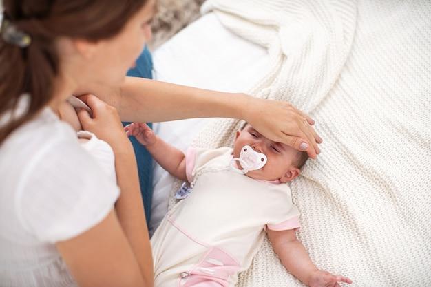 Jovem mãe animada verifica a temperatura do seu filho recém-nascido
