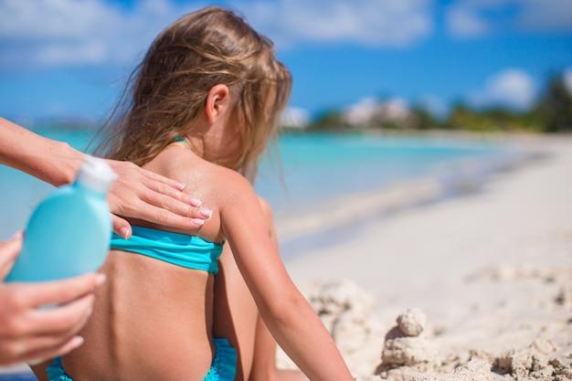 Jovem, mãe, aplicando, sunblock, creme, ligado, filha pequena, ombros