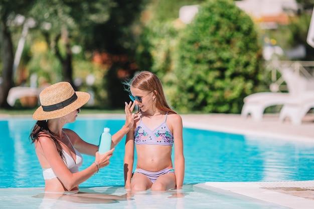 Jovem mãe aplicar protetor solar no nariz da filha
