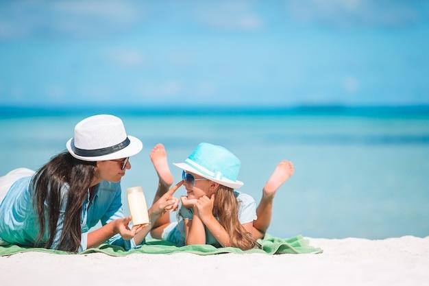 Jovem mãe aplicar protetor solar para filha
