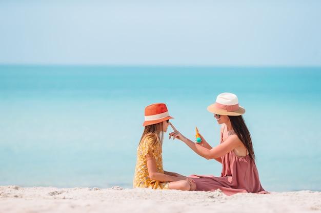 Jovem mãe aplicar protetor solar para nariz de filha na praia. proteção solar