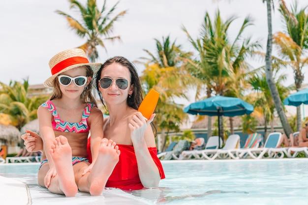 Jovem mãe aplicar protetor solar protetor no nariz da filha na praia.
