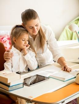 Jovem mãe apontando no livro de exercícios e explicando o dever de casa para a filha