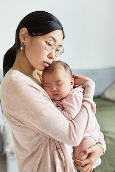 Jovem mãe asiática abraçando sua filha e amando-a enquanto ela dormia sobre as mãos