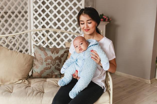 Jovem mãe asiática e bebê na sala.