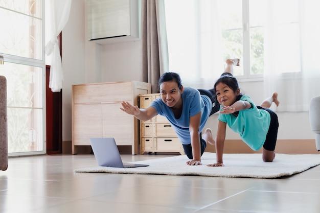 Jovem mãe asiática e sua filha fazendo alongamento exercícios de ioga ioga juntos em casa. os pais ensinam a criança a se exercitar e a manter a saúde física e o bem-estar na rotina diária.