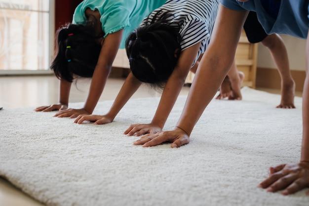 Jovem mãe asiática e suas filhas fazendo alongamento e ioga exercícios de fitness juntos em casa. pais e filhos exercem-se para serem fortes e manter a saúde física e o bem-estar na rotina diária.