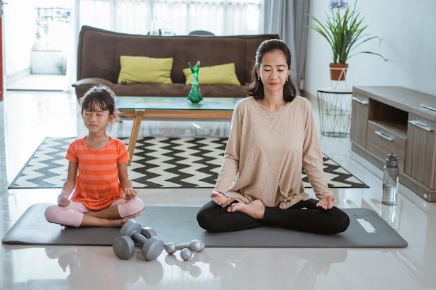 Jovem mãe asiática fazendo exercícios de ioga em casa com a filha.
