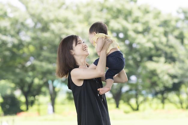 Jovem mãe asiática segurando um bebê em um parque verde