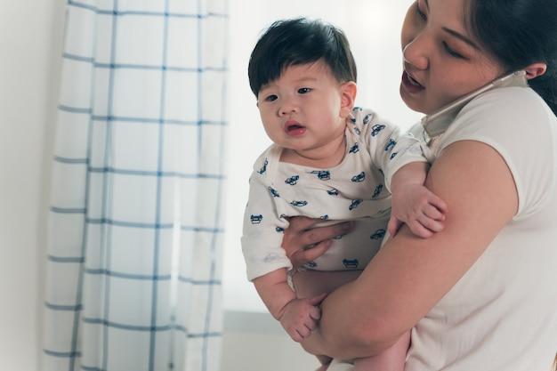 Jovem mãe asiática segurando um bebê enquanto fala ao telefone