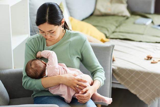 Jovem mãe asiática sentada na cadeira e alimentando sua filha pela manhã no quarto