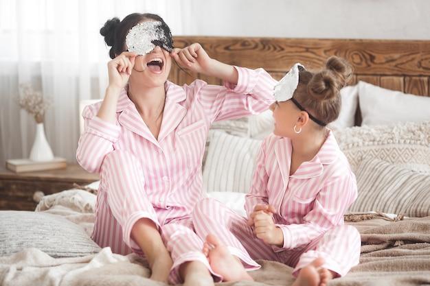 Jovem mãe ativa e sua filha se divertindo juntos em casa no quarto de pijama
