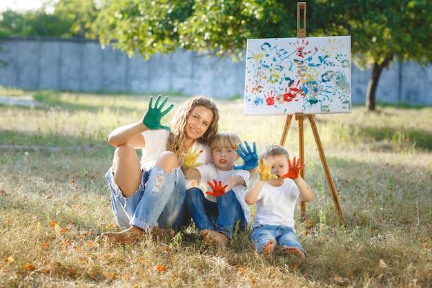 Jovem mãe atraente se divertindo com seus filhos no parque. família alegre se divertindo ao ar livre. mãe brinca com seus filhos.