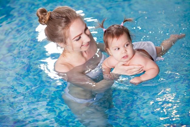 Jovem mãe banha o bebê na piscina.