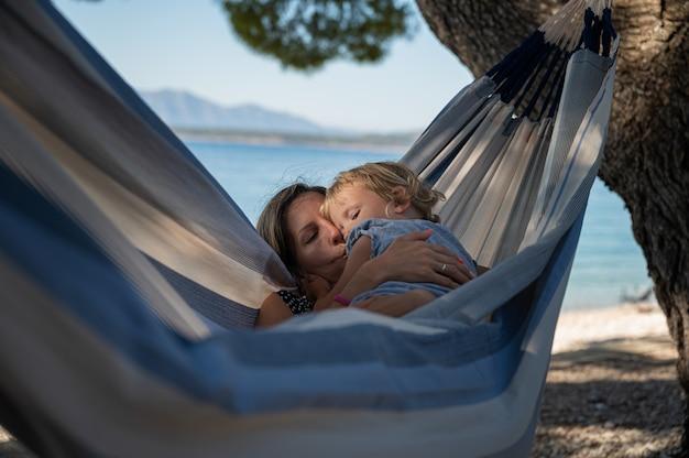 Jovem mãe beijando a filha pequena enquanto desfrutam de um tempo juntos, pendurados em uma rede na praia.