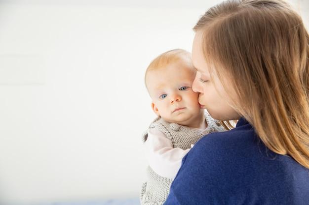 Jovem mãe beijando criança infantil fofa