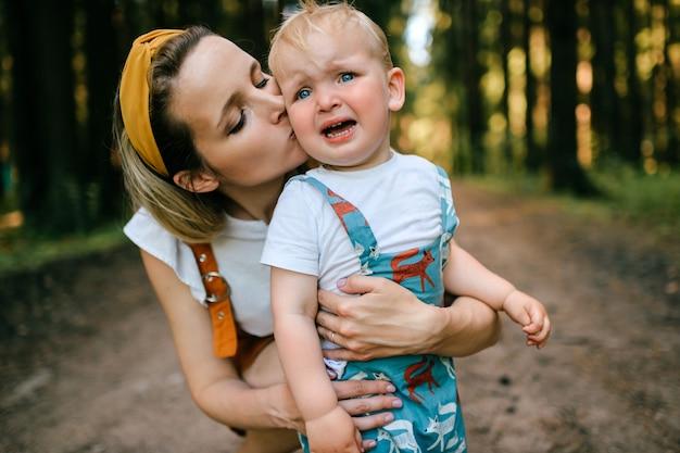 Jovem mãe beijando seu filho chorando na floresta