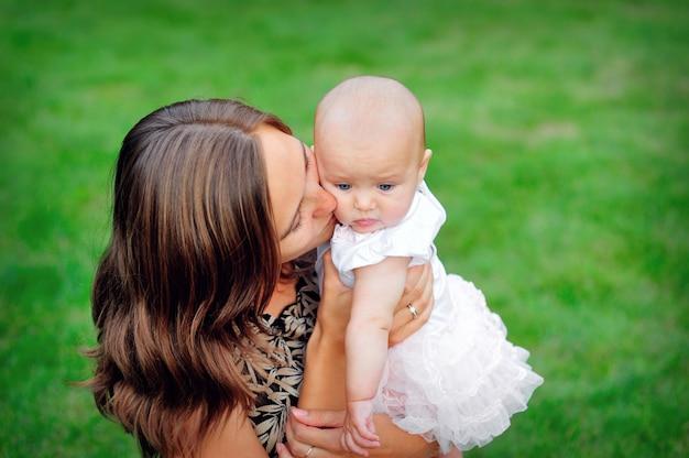 Jovem mãe beijando sua filha bebê