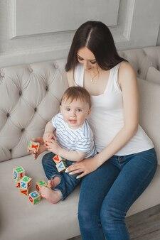 Jovem mãe bonita brincando com seu filho pequeno. família alegre se divertindo dentro de casa com o filho bebê