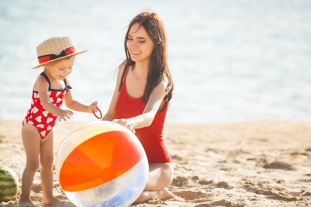 Jovem mãe bonita brincando com sua filha bonita na praia. mãe amorosa se divertindo com seu filho na praia do mar