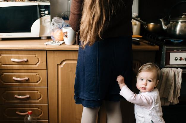 Jovem mãe bonita de cabelos longos, preparando comida na cozinha para sua filha pequena.