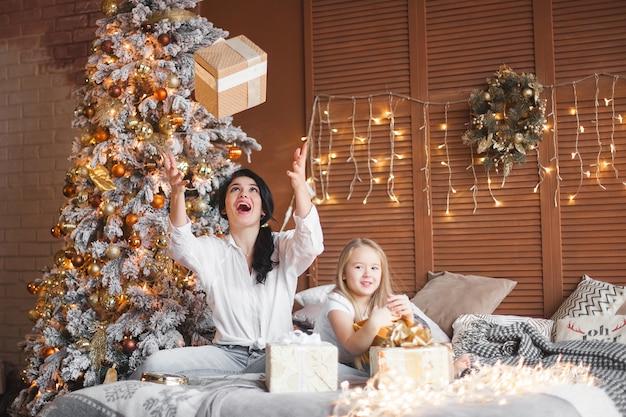 Jovem mãe bonita e sua filha compartilhar presentes de natal