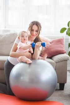 Jovem mãe bonita malhando com seu filho pequeno em casa