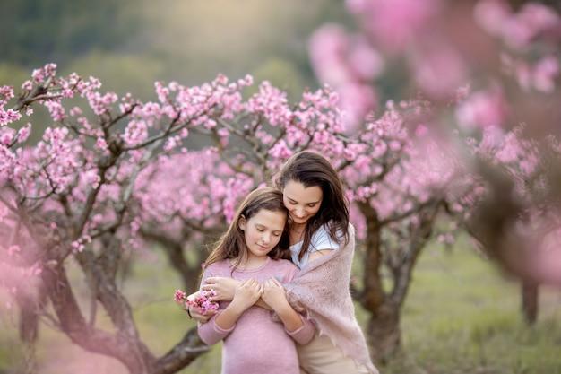 Jovem mãe bonita na primavera, árvore florescendo rosa no fundo.