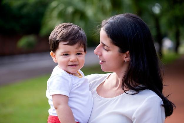 Jovem mãe brasileira com filho no fundo no parque.