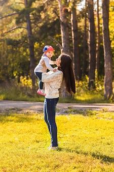 Jovem mãe brincando com a filha no parque outono.
