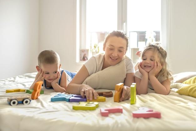 Jovem mãe brincando com seus filhos em uma cama sob a luz do sol através das janelas