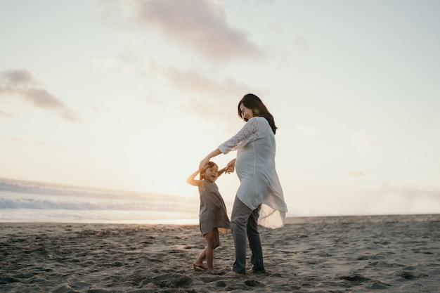 Jovem mãe brincando com sua filha à beira-mar