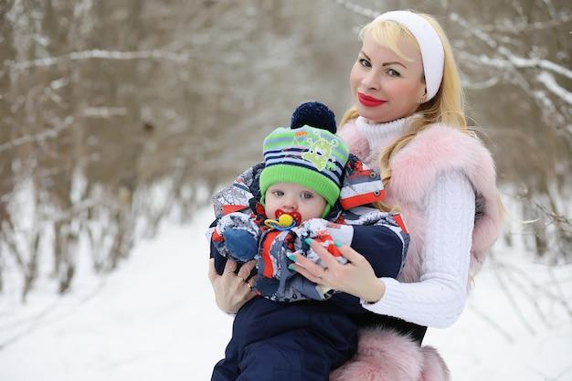 Jovem mãe caminha em um dia de inverno com um bebê nos braços no parque