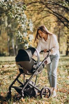 Jovem mãe caminhando com carrinho de bebê