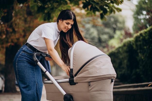 Jovem mãe caminhando com stoller no parque
