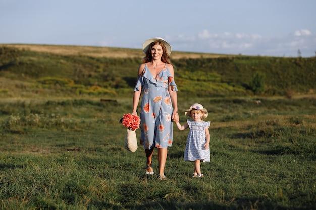 Jovem mãe caminhando com sua filha no campo verde. feliz dia das mães. fechar-se.