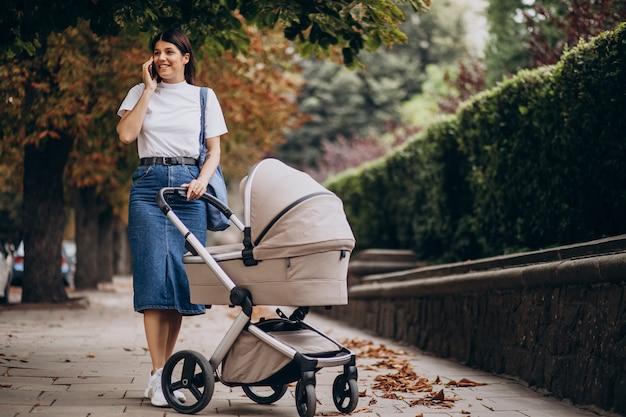 Jovem mãe caminhando com um carrinho no parque e falando ao telefone