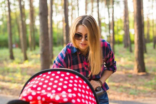Jovem mãe caminhando e empurrando um carrinho de bebê no parque. mãe passeando com o recém-nascido. linda mãe feliz com carrinho de bebê ao ar livre.