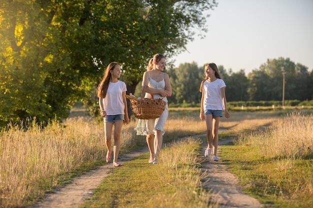 Jovem mãe caminhando para fazer um piquenique com suas duas filhas