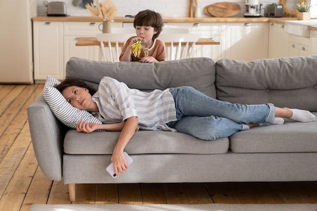 Jovem mãe cansada de criança hiperativa mãe deprimida deitada no sofá estressada com o barulho precisa de descanso