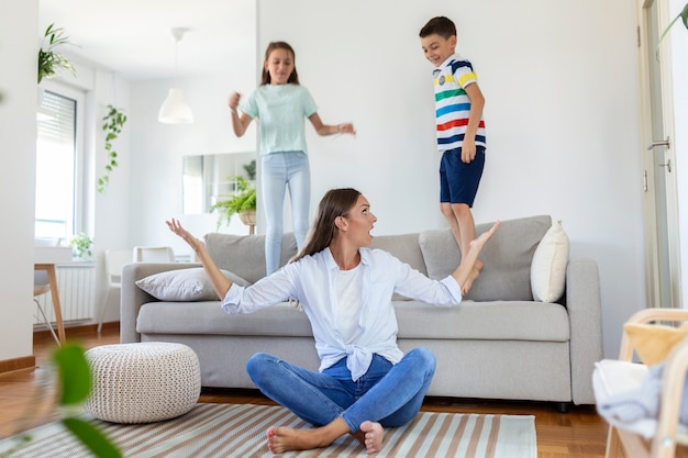 Jovem mãe cansada, sentada no chão, trabalhando com laptop e documentos, enquanto as crianças pequenas, pulando no sofá, se divertindo e fazendo barulho